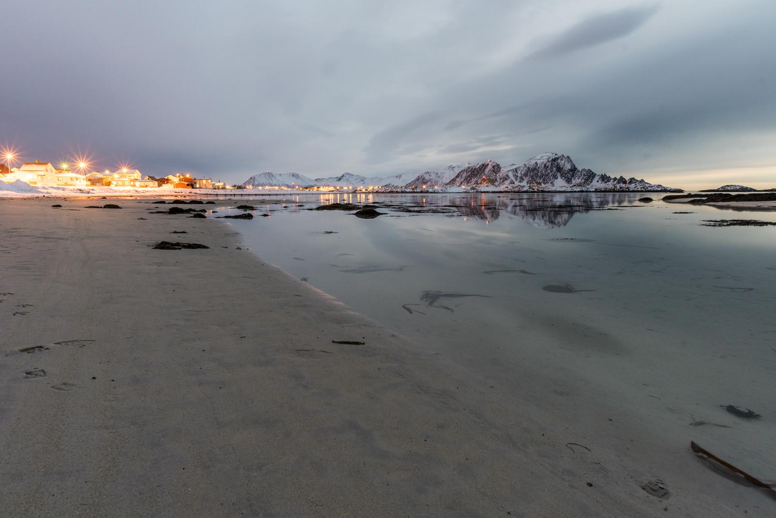 Spiaggia di Andenes con case illuminate poco dopo il tramonto